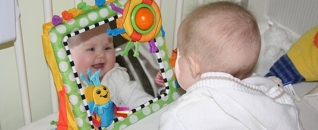 Baby looking into mirror